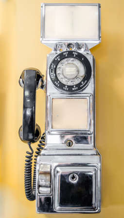 Vintage, out of service, retro, chrome plated, old style, coin operated, public, pay telephone from an earlier time in technology. Stock fotó