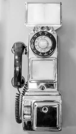 Vintage, out of service, retro, chrome plated, old style, coin operated, public, pay telephone from an earlier time in technology in black & white.