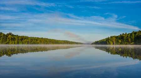 swampy: Bright mid-summer blue sky, misty morning in the middle of Corry lake.   Warm water and cooler air at daybreak creates misty patches along shoreline.  Still water along a calm, quiet lakeside.