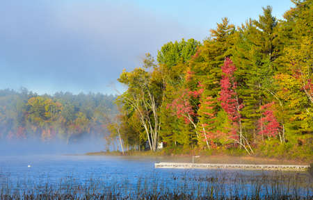 Late-summer, morning sun shines on mist rising from warmer woodland lake water.  Dock extends from lakeside cottage country in a deciduous waterfront forest.