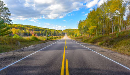 Sunny road to anywhere, single point perspective down a country highway in summer.  Warm day to drive or travel to anywhere. Stock Photo