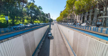Street scene in Madrid.  Sun shines bright on Calle del Alfonso where it enters a tunnel that runs under an intersection, above.  Car travels down Alfonso XII   Street toward tunnel entrance.