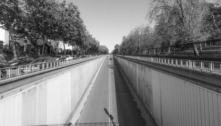 Black & white street scene in Madrid.  Sun shines bright on Calle del Alfonso where it enters a tunnel that runs under an intersection, above.  Car travels down Alfonso XII   Street toward tunnel entrance. Stock Photo