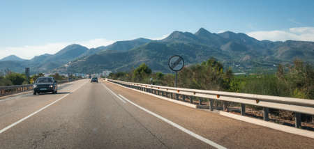 blacktop: Sunshine on Coastal highway.  Traffic moves along through foothills and mountain ranges on the edges of continental Europe in Spain.