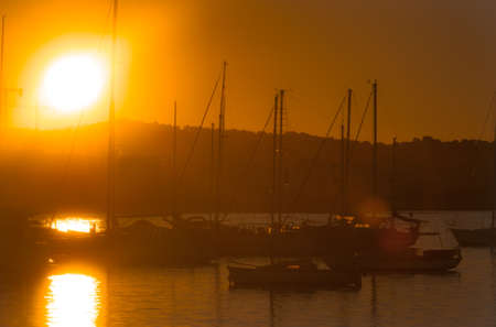 Sailboat silhouettes, magnificent golden warm sunset in Ibiza marina. Magnificent golden warm sunset in Ibiza marina.