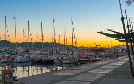 gefesselt: Segelboote und kleine Yachten am Hafen von Ibiza am Abend. Herrlicher goldener warmer Sonnenuntergang am Ende des Tages.