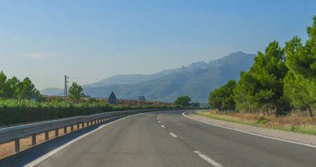 Around the bend - Sunshine on Spanish coastal highway.   Driving view of foothills and mountain ranges on the edges of continental Europe in rural Spain. Stock Photo