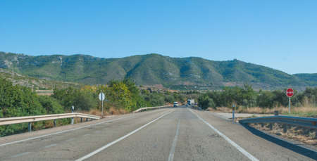 blacktop: View down the highway through coastal foothills and mountains of rural Spain. Stock Photo