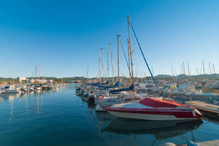 Ibiza sunshine in Late afternoon in St Antoni de Portmany, Ibiza, Spain.  Row of idle watercraft, sailboats & yachts.  Boat in foreground needs paint job. Stock Photo