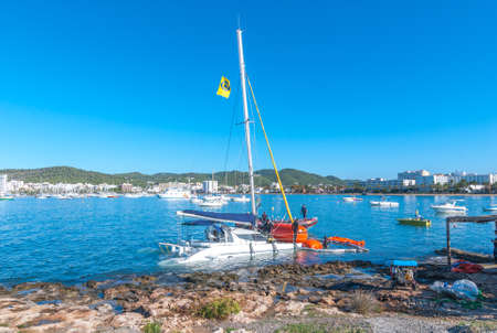 Sant Antoni De Portmany, Ibiza, November 6th, 2013:   Post thunderstorm blues.  Bright morning sees a dive crew work to recover a crippled partially submerged catamaran boat that broke free from its mooring during an overnight storm.