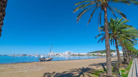 Mid morning sun, along beach near the city, sees an abandoned sailboat.  Rows of palm trees line the beach, sunny day along the waters edge in Ibiza, St Antoni de Portmany Balearic   Islands, Spain.