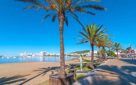 Ibiza sunshine on the waterfront in Sant Antoni de Portmany,  Take a walk along the main boardwalk, now a stone concourse, beside the beach in warm morning sunshine. Stock Photo