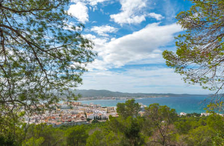 zoomed: View through the trees, from hillside of nearby town: San Antonio Sant Antoni de Portmany in the Balearic Islands, Ibiza, Spain.