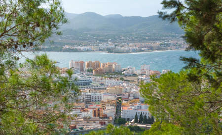 zoomed: View through naturally framing trees, from hillside of nearby town: San Antonio Sant Antoni de Portmany in the Balearic Islands, Ibiza, Spain. Stock Photo