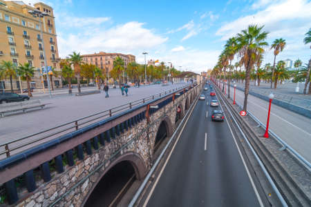 Barcelona, Spain, Nov 3rd, 2013:  Tourism in Spain.   Off season traffic in tunnelled streets & pedestrian traffic above as people enjoy walking outdoors along the waterfront in warm weather in November.
