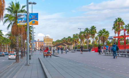 guardrails: Barcelona, Spain, Nov 3rd, 2013: Tourism economy in Europe, people ride in a rickshaw, on bicycles & walking, taking advantage of warm weather.  Young people walk their dog along the citys palm tree lined roads.