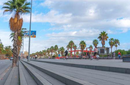 blacktop: Barcelona, Spain, Nov 3rd, 2013: Tourism economy - Urban outdoors, people take advantage of warm weather.  Walking, running, bicycling & exercising.
