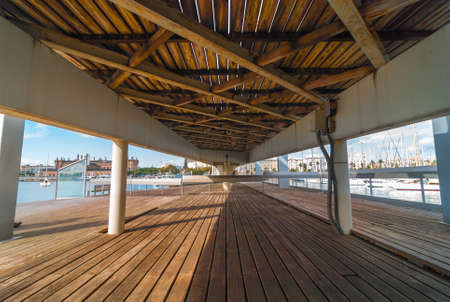View toward shoreline & city waterfront from under the raised pedestrian walkway concourse & bridge at Port Vell marina shopping centre in Barcelona, Spain. Stock Photo