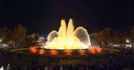 A crowd of people at colourful light & water fountain show.  Night at the Magic Fountain in Barcelona. Large water attraction turns on at night & provides entertainment for all ages on a warm evening.