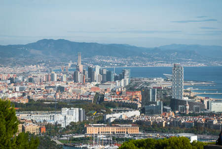 famous industries: Cable car view of Barcelona city and coastline of Spain.   Balearic sea & coastline of modern cosmopolitan city seen from high, cable car over the city.