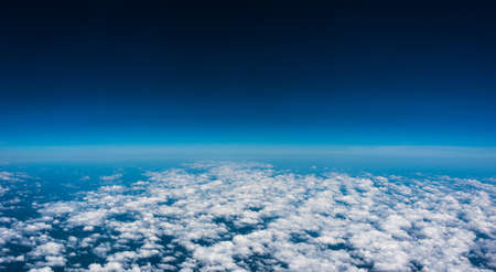 Above the clouds.  High flight and view of near edge of space at 35,000 feet.  Looking out the air plane window.