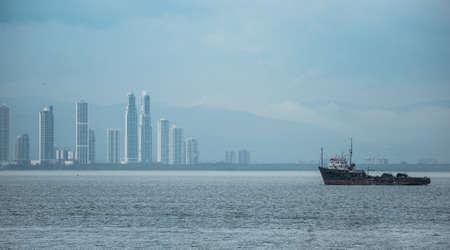 Large tug boat near the Panama Canal with Panama City skyline at the back