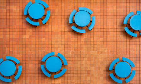Orange square tile patio and empty, round blue tables in a random geometric shapes pattern Stock Photo