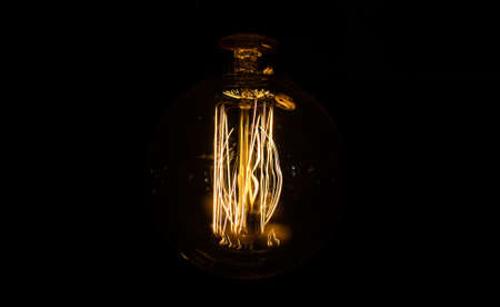 Large long electric incandescent filament in a retro style light bulb glows and reflects warm light.