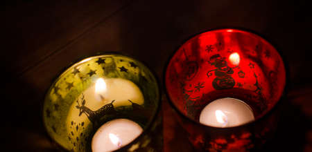 Christmas candle holders alight with a holdiay red glow, depicts scenes of winter and snow by the flame within.
