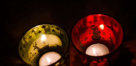 Christmas candle holder alight with a holdiay red glow, depicts scenes of winter and snow by the flame within.