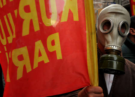 gasmask: A Protestant with a gas mask on his face and flag protests on the street