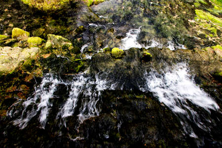 A small waterfall within the river sources of the river Bosna. The photo was taken from above at a slow shutter speed and parts of the shore can be seen covered with green vegetation on the rocks.