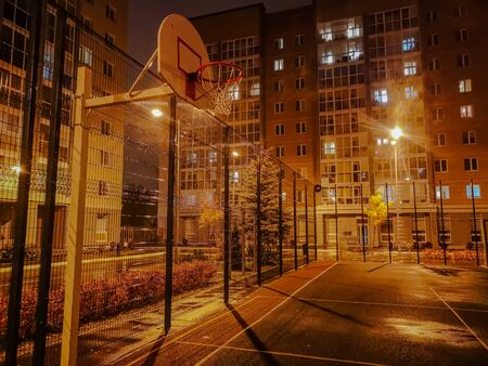 Basketball court with metal grille in yard at night in light of lights in overcast weather with yellow shade