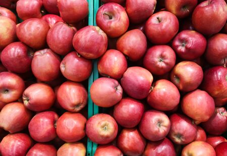 red apples in crates for sale in a mall in the department of vegetables and fruits.
