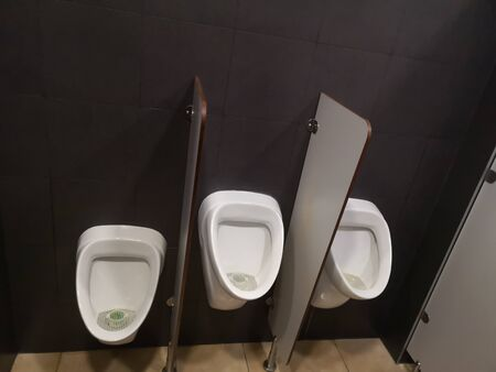 two adult urinals and one for children white porcelain urinal with flush system in a public mens restroom.