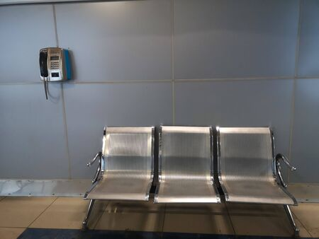 Three metal chairs and landline in metro station train waiting room.