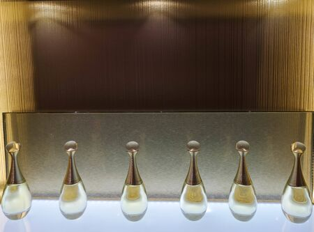 Perfume bottles of toilet water stand on a shelf with illumination.