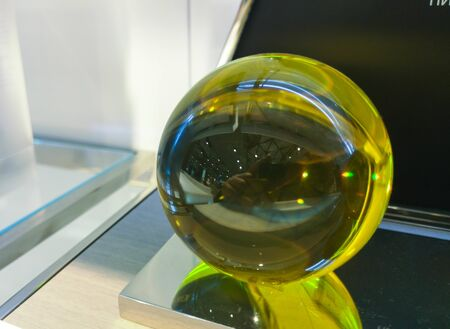 Green glass ball in the form of a sphere with emerald tint on a glass shelf with cold illumination. 版權商用圖片