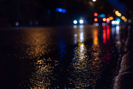 The blurred focus of the city road and car during rain at night, with colorful unfocused lights on the rear background. Water from the rain and an abstract image of the side of the lights in the city