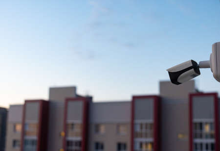 CCTV camera on the roof of a multi-level parking lot with a residential building in the background at dawn