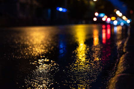 Blurred focus of a freeway during night rain with multicolored out-of-focus lights in the background. Water from the rain and the reflection of lanterns in the city. Banco de Imagens