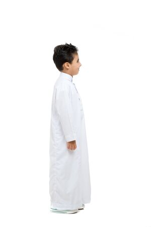 Arab boy standing sideways, wearing white traditional Saudi Thobe and sneakers, raising his hands on white isolated background