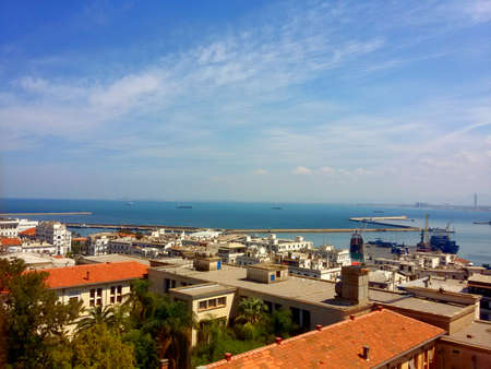 A photo taken on a sunny spring day of april 2017 where the garden of Algiers university can be seen, and in the background the mediterranean see and part of the port of Algiers.
