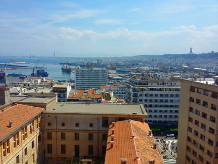 A photo taken during april 2017 of Algiers bay as viewed from the university, can be seen : a part of Algiers university buildings, place Audin (partly) down in the middle, the port of Algiers, the sanctuary of martyrs in the background on the right an Editorial