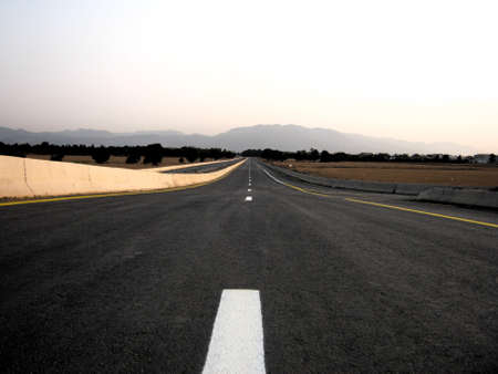 An empty road to the Atlas moutains crossing a (public) harvested barley field. Stock Photo