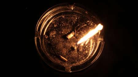 Burning match in ashtray on black background