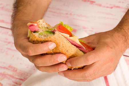 close-up man holding a sandwich with small bite