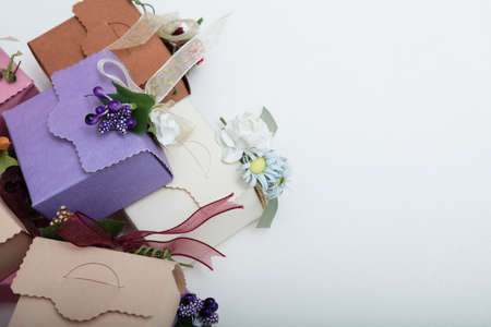 Special kind of gift boxes with ribbon and flowers on white backgroung, top view