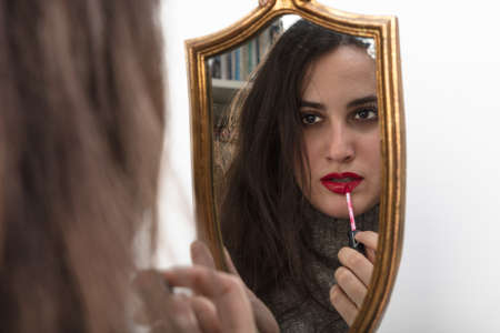 Beautiful woman applying red lipstick using a handheld gold framed vintage mirror with focus to her reflection in the glass Stock Photo