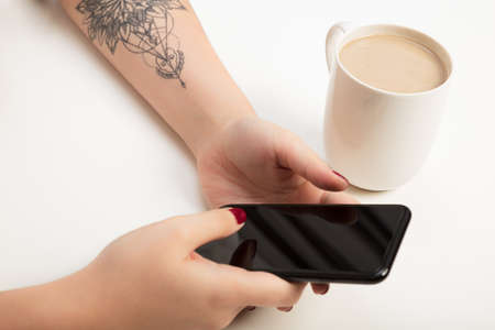 Woman banking , shopping or booking on a mobile phone in a close up view of her hands and the blank screen alongside a mug of coffee or tea